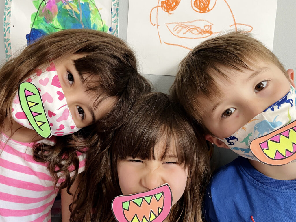 3 Happy Children show off the face masks they've made for Halloween